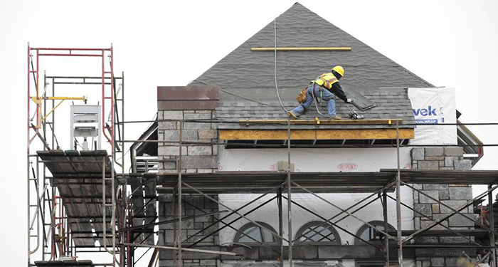 Roofers work on the roof at the new Barrington Village Center along Main Street in downtown Barrington on May 5, 2015. Critics of the 31,000-square-foot development lament that it is pulling businesses from elsewhere in the suburb, causing vacancies. Stacey Wescott / Chicago Tribune