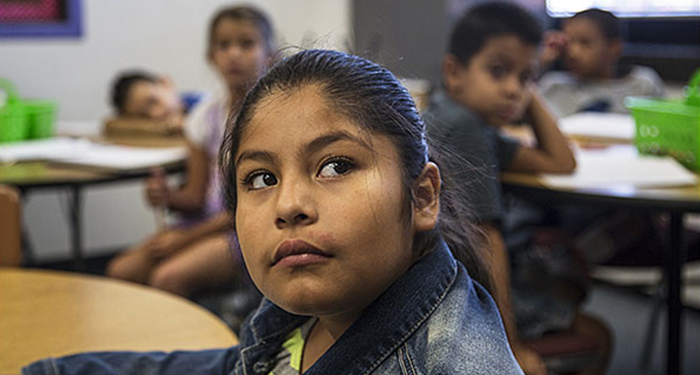 Maritza Fabia, a 3rd grader at Rose Hill Elementary School in Colorado's Adams 14 school district, listens to her teacher during a Spanish class. The district is under a federal compliance agreement to correct discrimination problems. —Nathan W. Armes for Education Week