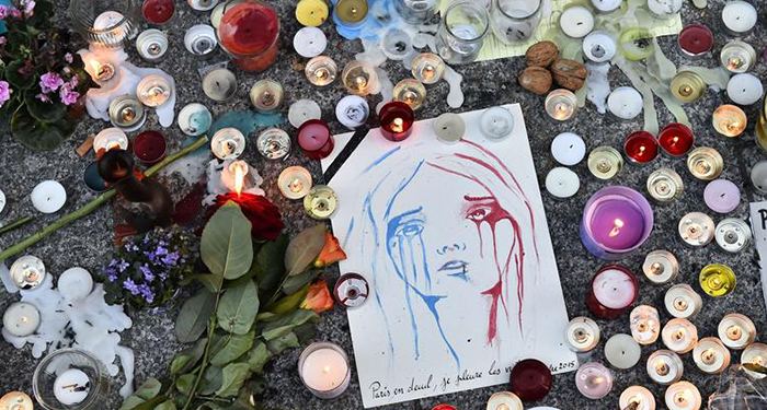 "Candles have been lit at a makeshift memorial in front of ""Le carillon"" restaurant one of the site of the attacks in Paris on November 15, 2015, in the 10th district of Paris. (LOIC VENANCE / AFP/Getty Images)"