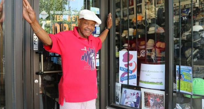 "Bernard Shannon, owner of Bernard's Wear in South Chicago, is shown next to a poster in his shop advertising the ""Shakespeare in the Parks"" program. [Provided]"