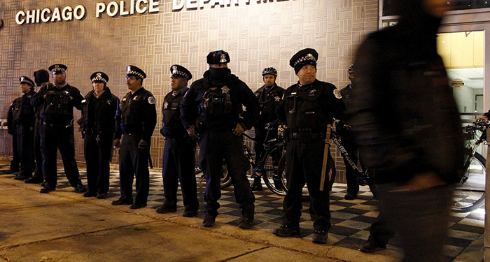 A protester walks past a line of police officers standing guard in front of the District 1 police headquarters in Chicago, Illinois November 24, 2015. Photo by REUTERS/Frank Polich